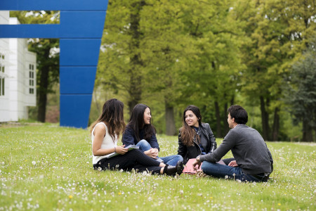 A group of students sitting on the grass at HEC Paris