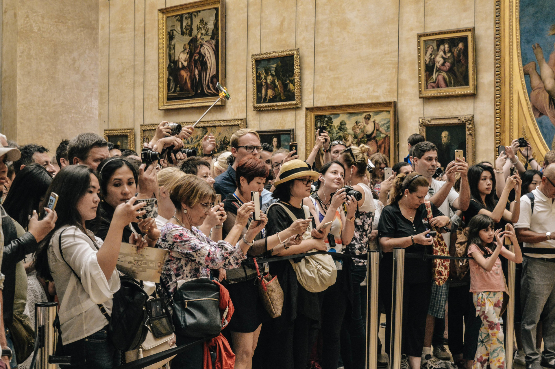 A large group of people taking pictures at a museum
