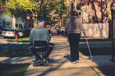 A wheelchair user and a woman using a cane side by side