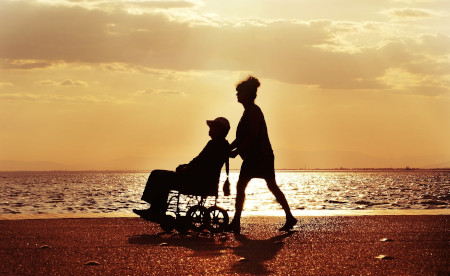 A wheelchair user is pushed by a friend at the beach