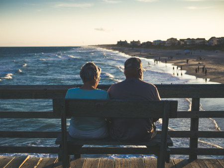 People with invisible disabilities sitting on a bench at the beach