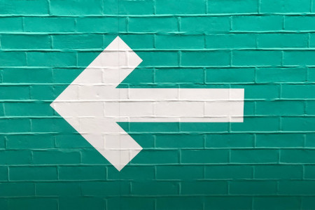 A white arrow pointing left on a green wall